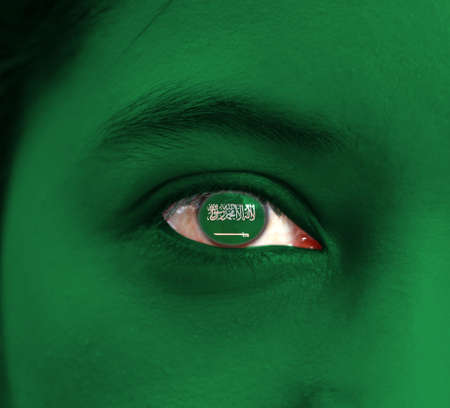 Human face painted Saudi Arabia flag with the Shahada or Muslim creed written in the Thuluth script above a saber on the center of eye or eyeball. Human eye painted with flag of Saudi Arabia.