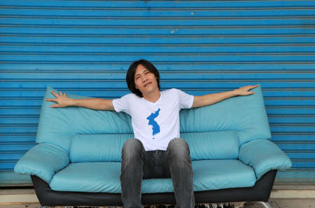Asian man wearing Unification Korea flag color shirt sitting and extend the arms on the blue sofa with blue background.