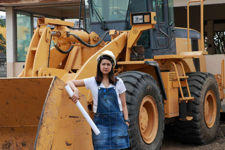 Female civil engineer or architect with white helmet and project drafts while in hand standing with Alloy Bulldozer Truck with Front Loader Truck Engineering Construction Car Vehicle at the work area. Standard-Bild - 134472937