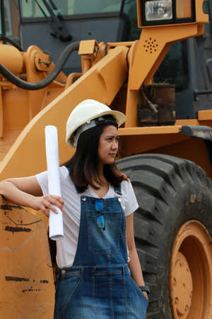 Female civil engineer or architect with white helmet and project drafts while in hand standing with Alloy Bulldozer Truck with Front Loader Truck Engineering Construction Car Vehicle at the work area. Standard-Bild - 134472942
