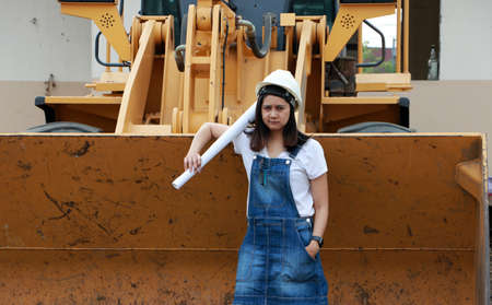Female civil engineer or architect with white helmet and project drafts while in hand standing with Alloy Bulldozer Truck with Front Loader Truck Engineering Construction Car Vehicle at the work area. Standard-Bild - 134472945