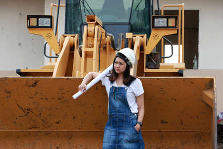 Female civil engineer or architect with white helmet and project drafts while in hand standing with Alloy Bulldozer Truck with Front Loader Truck Engineering Construction Car Vehicle at the work area. Standard-Bild - 134472949