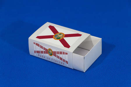 Florida flag on white box with barcode and the color of state flag on blue background, paper packaging for put match or products. The concept of export trading from Florida.