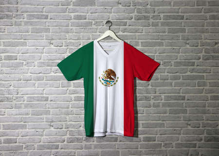 Mexico flag on shirt and hanging on the wall with brick pattern wallpaper, a vertical tricolor of green white and red with the nation Coat of Arms centered on white.