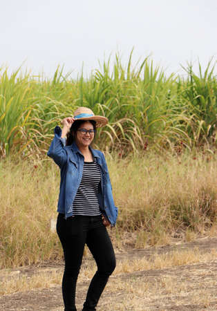 Woman agriculturist standing with the hand on her hat and wearing Long-sleeve denim shirt on the sugarcane farm background. Her face Happy expression.