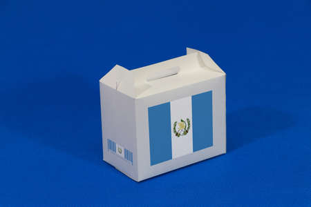 Guatemala flag on white box with barcode and the color of country flag on blue background. The concept of export trading from Guatemala, paper packaging for put products. Standard-Bild