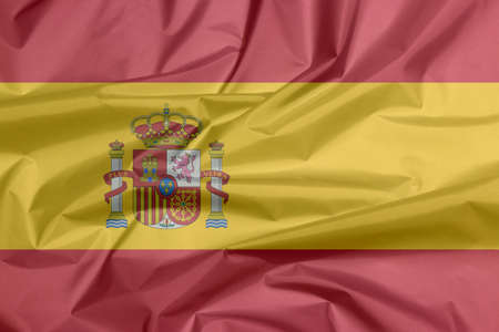 Fabric flag of Spain. Crease of Spanish flag background, a horizontal of red yellow and red; charged with the Spanish coat of arms left of center.