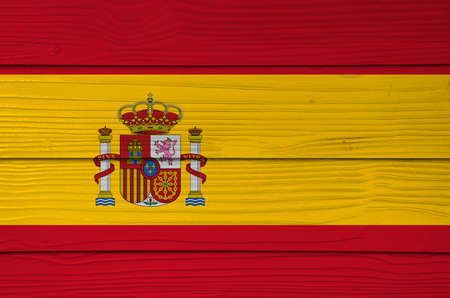Spain flag color painted on Fiber cement sheet wall background, a horizontal of red yellow and red; charged with the Spanish coat of arms left of center.