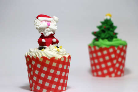 Christmas cupcakes decorated with Santa Claus and out focus Christmas tree cupcakes on white background. Stock Photo