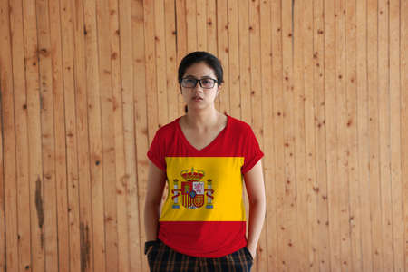 Woman wearing Spain flag color shirt and standing with two hands in pant pockets on the wooden wall background, a horizontal of red yellow and red; charged with the Spanish coat of arms left of center.