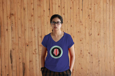 Woman wearing Bougainville flag color shirt and standing with two hands in pant pockets on the wooden wall background. Red and white upe headdress superimposed on a green and white kapkap, on a field of cobalt blue.
