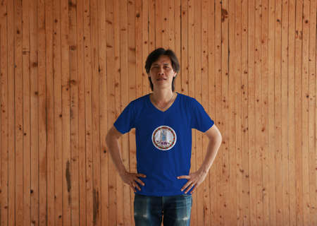 Man wearing Virginia flag color shirt and standing with akimbo on the wooden wall background. Obverse of the Seal of Virginia on an azure field. The states of America.