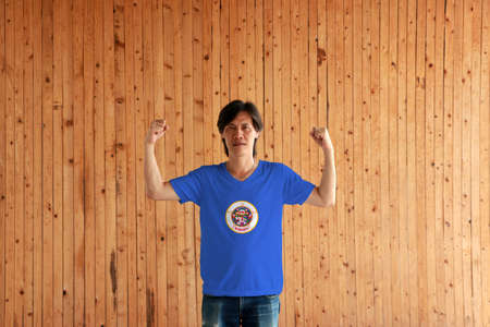 Man wearing Minnesota flag color of shirt and standing with raised both fist on the wooden wall background, State seal on a medium blue field.