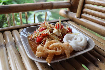 Green papaya salad with salted egg and rice Noodles with crispy Pork Skin in the square dish on the bamboo flooring. Stock Photo