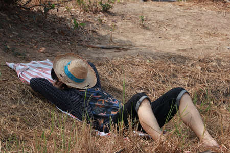 Agriculturist male use the loincloth on the floor for relax sleeping with a hat close the face on nature. Фото со стока