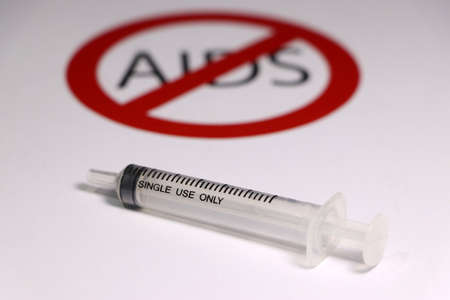 A syringe on white floor with out focus symbolic of no or anti AIDS.