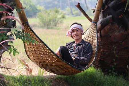 Agriculturist male with loincloth wrapped over the head lying relaxed in the basketry crib on the nature. Фото со стока