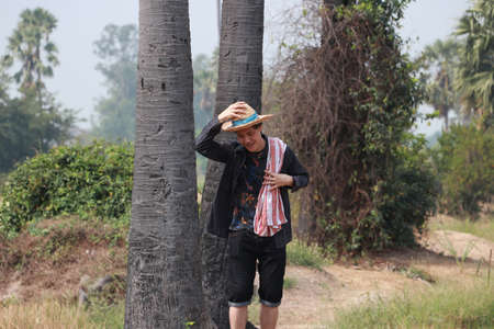 Agriculturist male wear a hat and and his hand on the hat with loincloth across the shoulder near the trunk of sugar palm and standing on nature.