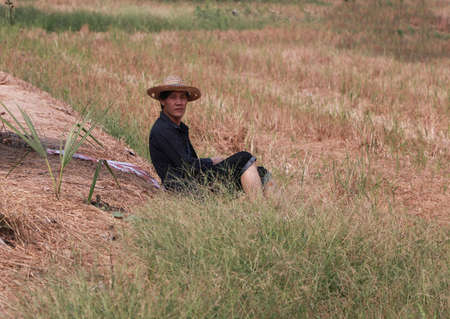Agriculturist male use the loincloth on the floor for relax sitting and wear the hat on nature.