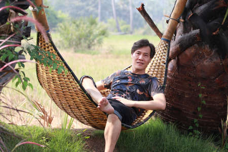 Agriculturist male sit relaxing in the basketry crib on the nature. Фото со стока