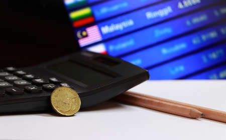 Fifty cents coin of Malaysia on the white floor with pencil and calculator on digital board of currency exchange money background, the concept of finance. Stok Fotoğraf