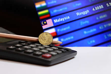 Fifty cents coin of Malaysia and pencil on the calculator with digital board of currency exchange money background, the concept of finance. Stok Fotoğraf