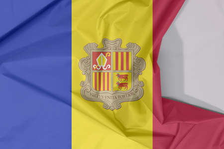 Andorra fabric flag crepe and crease with white space. A vertical tricolor of blue yellow and red with the National Coat of Arms on the center.