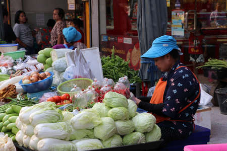Muang, Pathum Thani, Thailand - Feb 1, 2020 : Fresh vegetable vendor sitting at her shop in the fresh food market.