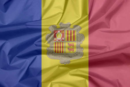 Crease of Andorra fabric flag background. A vertical tricolor of blue yellow and red with the National Coat of Arms on the center.