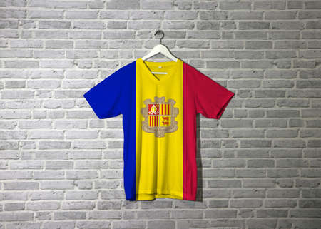 Andorra flag on shirt and hanging on the wall with brick pattern wallpaper. A vertical tricolor of blue yellow and red with the National Coat of Arms on the center.