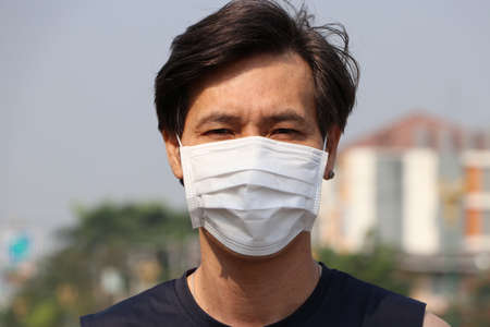Masked Asian man prevent germs. concept of Tiny Particle or virus corona protection.