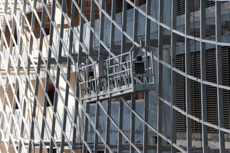 One hanging scaffold or construction platform outside of a building, being used for construction purpose. Stok Fotoğraf
