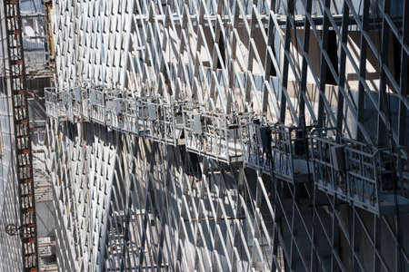 Many hanging scaffold or construction platform outside of a building, being used for construction purpose.