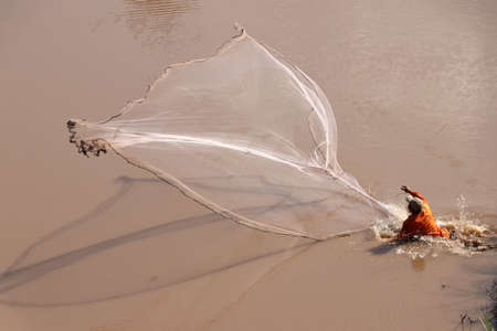 A fisherman throwing a net into the river for fishing.