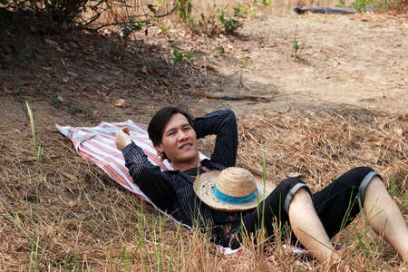Agriculturist male use the loincloth on the floor for laying relax with a hat on him at the nature. Фото со стока