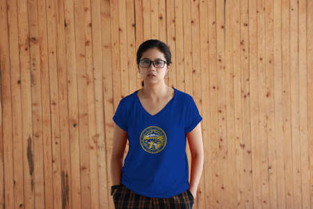 Woman wearing Nebraska flag color shirt and standing with two hands in pant pockets on the wooden wall background. Seal of Nebraska in gold on an azure field. The state of America. Stok Fotoğraf