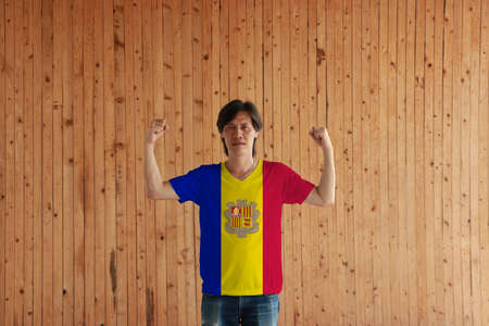 Man wearing Andorra flag color of shirt and standing with raised both fist on the wooden wall background, a vertical tricolor of blue yellow and red with the National Coat of Arms on the center. Stok Fotoğraf