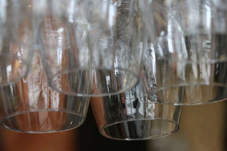 Clear glass for put wine hanging upside down on a rail at the counter bar.