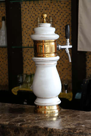 White and gold beer tap with classic design at a marble bar or counter bar.