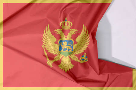 Montenegro fabric flag crepe and crease with white space. A red field surrounded by a golden border; charged with the Coat of Arms at the centre.