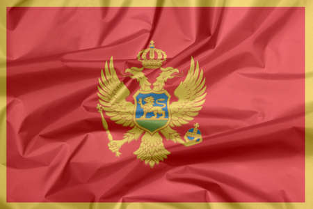 Crease of Montenegro fabric flag background. A red field surrounded by a golden border; charged with the Coat of Arms at the centre. Stok Fotoğraf