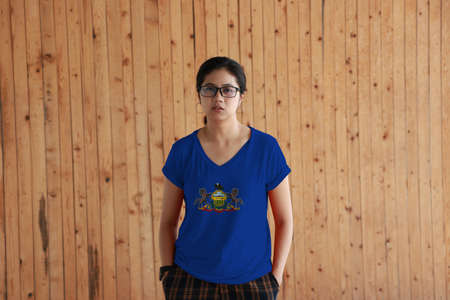 Woman wearing Pennsylvania flag color shirt and standing with two hands in pant pockets on the wooden wall background. Coat of arms of Pennsylvania on blue field. The state of America. Reklamní fotografie