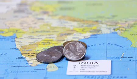 Heap of Rupee Indian money coins on the india map. Concept of money finance or travel.