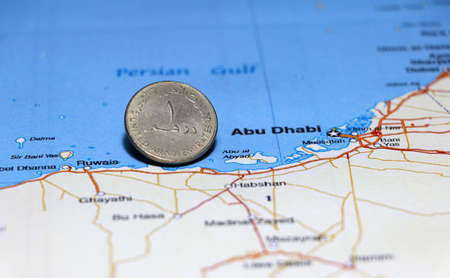 One coin of United Arab Emirates one dirham money on obverse put on the map near Abu Dhabi city. Concept of finance or currency or travel.
