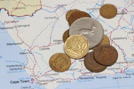 Heap of South African Rand coin money on on the map. Concept of finance or currency or travel.