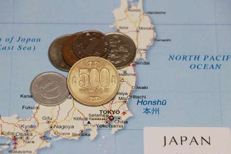 Heap of Japanese Yen coin money put on the Japan map. Concept of finance or currency or travel.