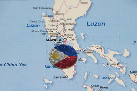 Pilipino flag on the coin of Philippine one peso money on the map near Manila city. Concept of finance or currency or travel.