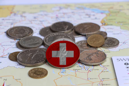 Switzerland flag on the coin with heap of Swiss franc money on the map. Concept of finance or currency or travel. Standard-Bild