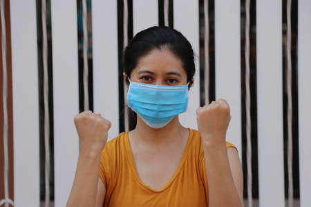 Masked Asian woman prevent germs. Tiny Particle or virus corona or Covid 19 protection. Lift the fist up for meaning fighting or concept of Combating illness.