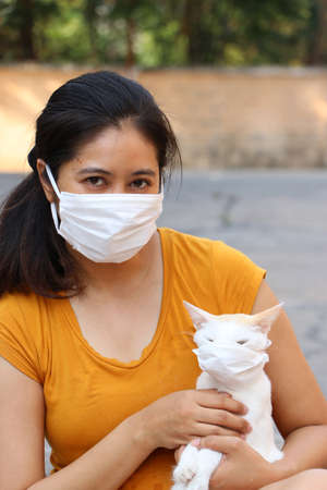 Masked Asian woman and her cat prevent germs. Tiny Particle or virus corona or Covid 19 protection.